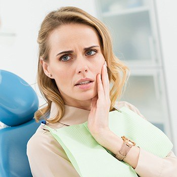 Woman holding cheek at emergency dentistry appointment