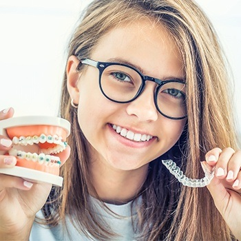Teen holding Invisalign tray and model smile with braces