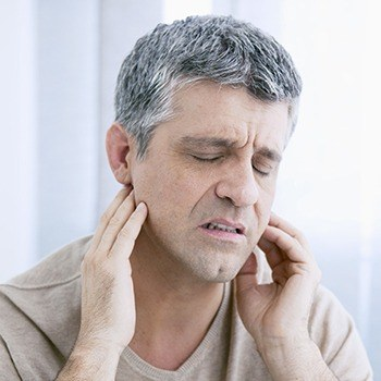 Man holding jaw joints in need of TMJ therapy