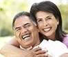 Older man and woman smiling outdoors after restorative dentistry